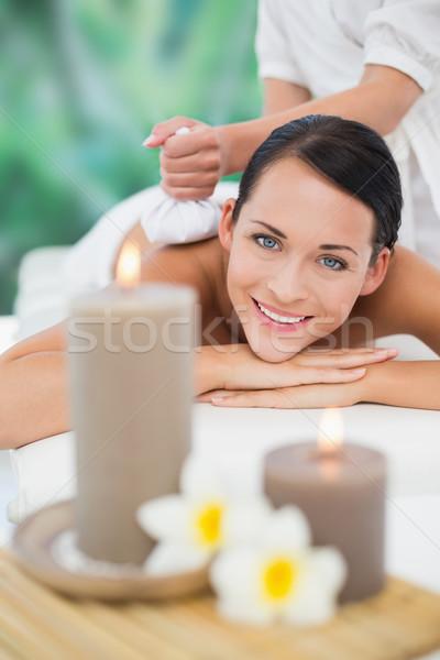 Beautiful brunette enjoying a herbal compress massage smiling at Stock photo © wavebreak_media