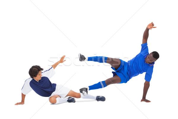 Football players tackling for the ball Stock photo © wavebreak_media