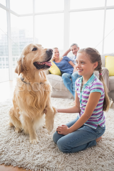 Girl playing with dog while parents relaxing at home Stock photo © wavebreak_media