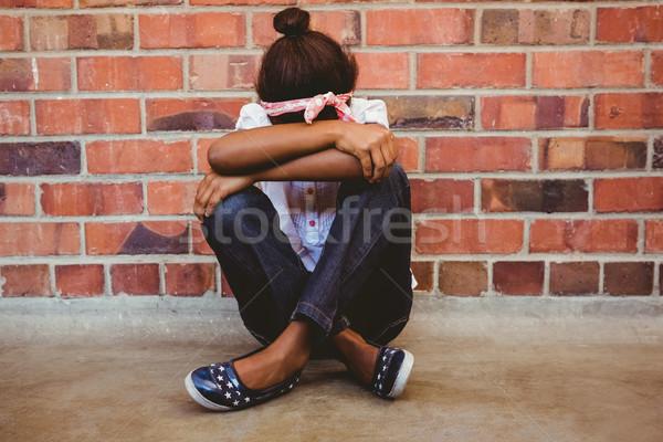Tensed girl sitting against brick wall in school corridor Stock photo © wavebreak_media