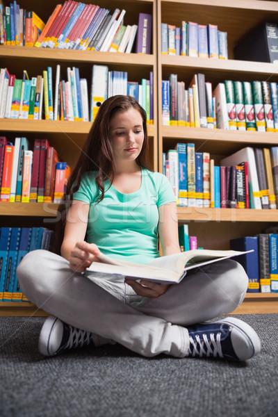 Student sitting on floor in library reading Stock photo © wavebreak_media