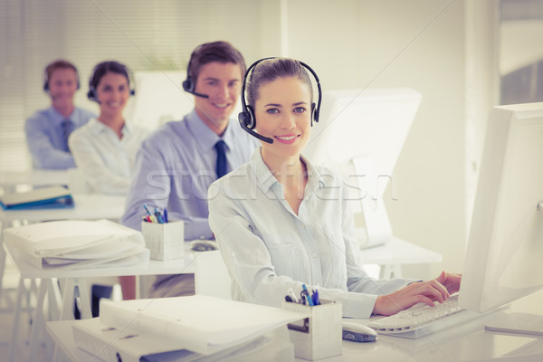 Stock photo: Business team working on computers and wearing headsets