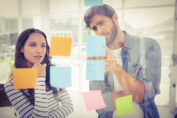 Puzzled business team looking post its on the wall Stock photo © wavebreak_media