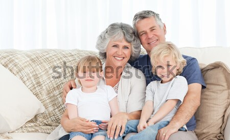 Stock photo: Happy parents with their children and puppy on floor