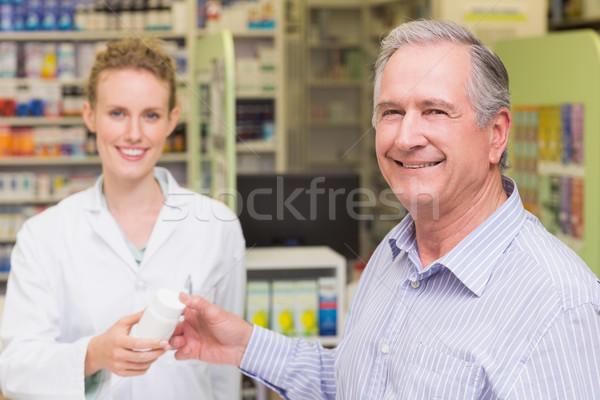 Pharmacist and costumer smiling a camera  Stock photo © wavebreak_media