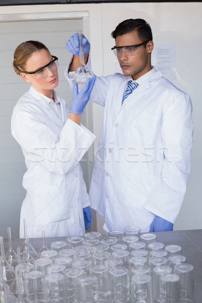Concentrated scientists looking at beaker  Stock photo © wavebreak_media
