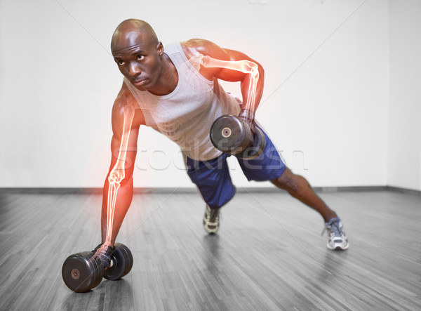 Highlighted arm of strong man lifting weights Stock photo © wavebreak_media