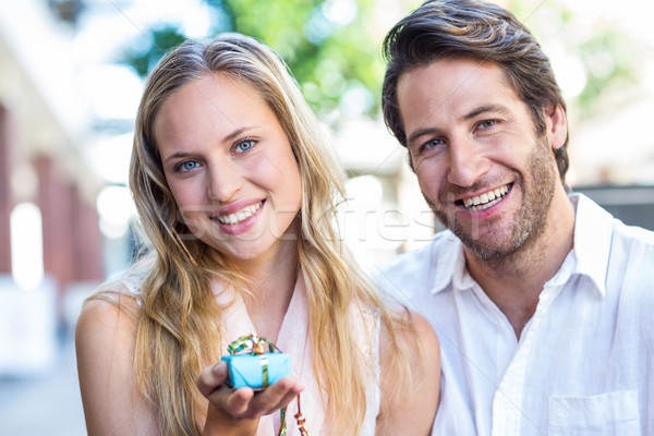 Smiling woman showing gift and sitting next to her boyfriend Stock photo © wavebreak_media