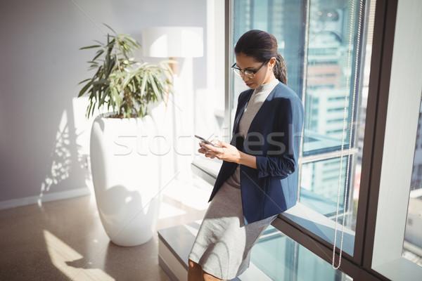 Attentif femme d'affaires téléphone portable couloir bureau verre Photo stock © wavebreak_media