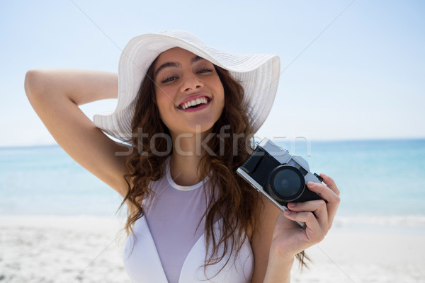 Portrait of woman with camera standing at beach Stock photo © wavebreak_media
