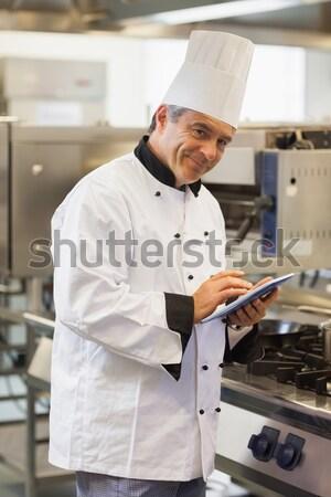 Női szakács néz vágólap kereskedelmi konyha Stock fotó © wavebreak_media
