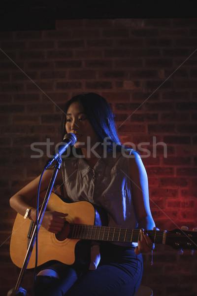 Sorridente feminino cantora jogar guitarra boate Foto stock © wavebreak_media