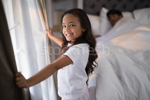 Portrait of of happy girl holding curtains in bedroom Stock photo © wavebreak_media