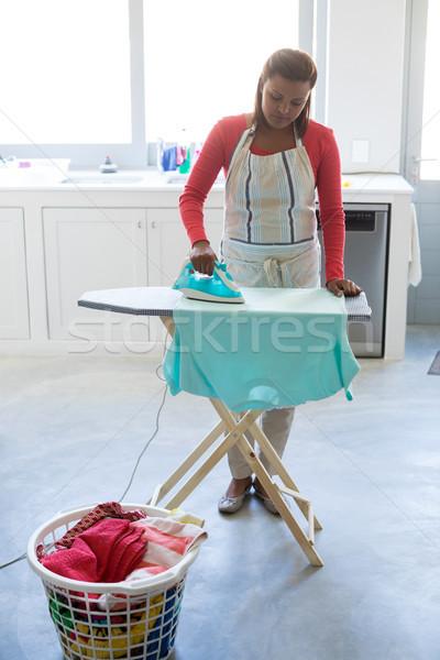 Woman ironing shirt on ironing board in kitchen Stock photo © wavebreak_media