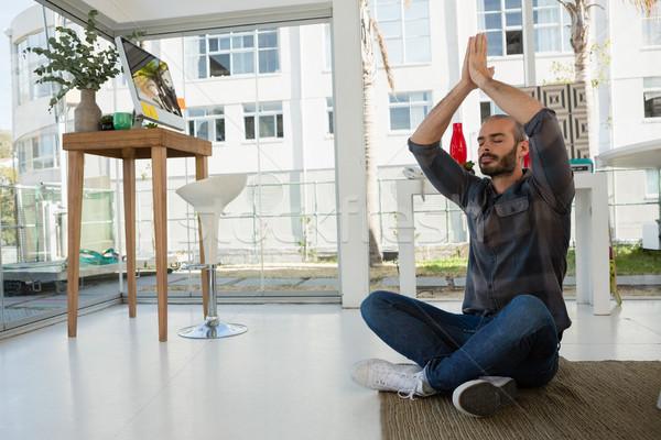 Projektant modlitwy pozycja posiedzenia piętrze Zdjęcia stock © wavebreak_media