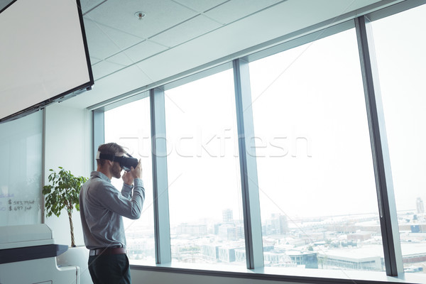 Businessman using virtual reality glasses while standing at office Stock photo © wavebreak_media