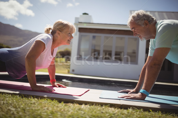 Senior couple doing push-up near swimming pool Stock photo © wavebreak_media