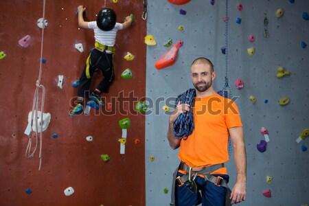 Male trainer guiding woman in climbing wall at club Stock photo © wavebreak_media