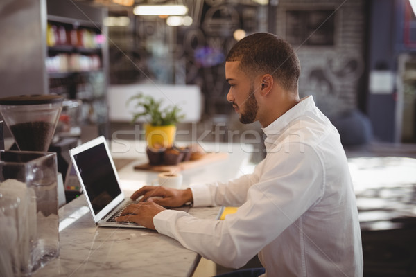 Yandan görünüş genç erkek sahip dizüstü bilgisayar kullanıyorsanız karşı Stok fotoğraf © wavebreak_media