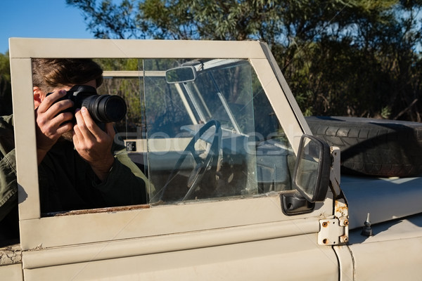 Man photographing while sitting in off road vehicle Stock photo © wavebreak_media