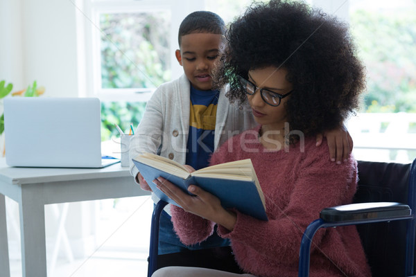 Son and his disabled mother reading a book Stock photo © wavebreak_media