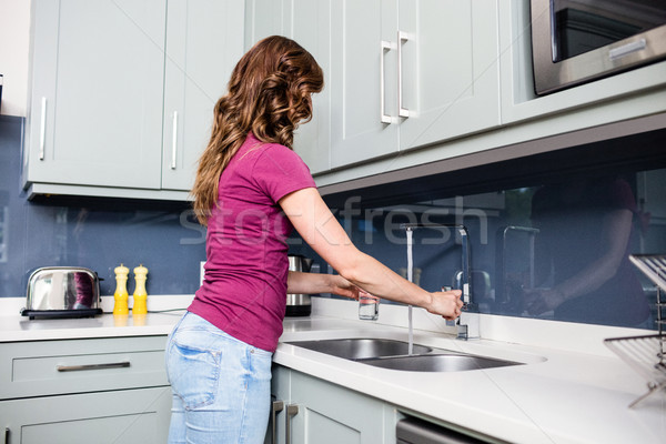 Woman filling water in glass at kitchen counter Stock photo © wavebreak_media