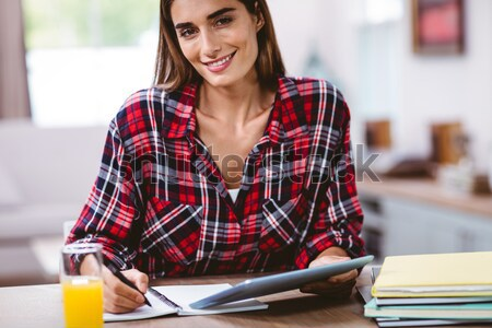 Portret glimlachende vrouw schrijven notepad laptop tabel Stockfoto © wavebreak_media