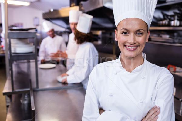 Happy chef standing in commercial kitchen in a restaurant Stock photo © wavebreak_media