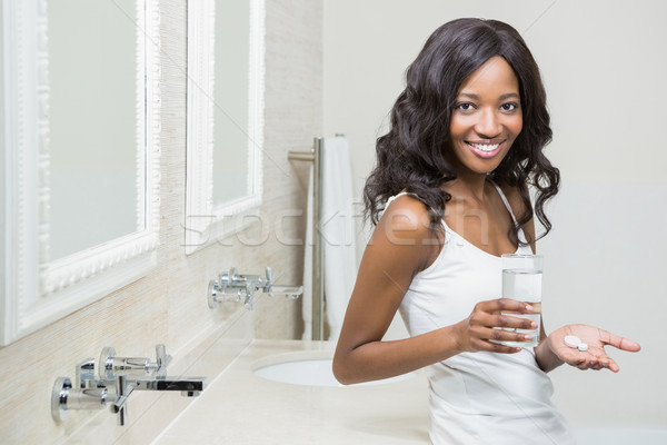 Beautiful woman holding pill and glass of water Stock photo © wavebreak_media