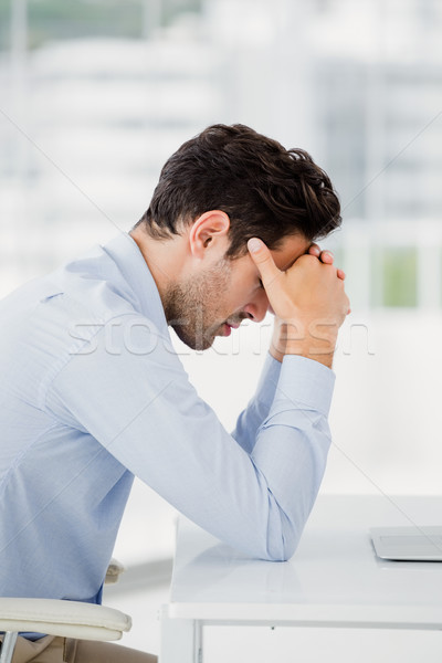 Tensed businessman sitting at table with hand on forehead Stock photo © wavebreak_media