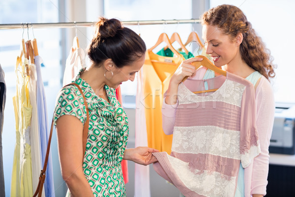 Woman selecting an apparel while shopping for clothes with her friend Stock photo © wavebreak_media