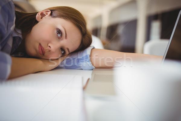 Tired businesswoman leaning on desk in creative office Stock photo © wavebreak_media