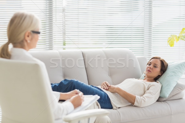 Woman lying on sofa while talking to therapist Stock photo © wavebreak_media