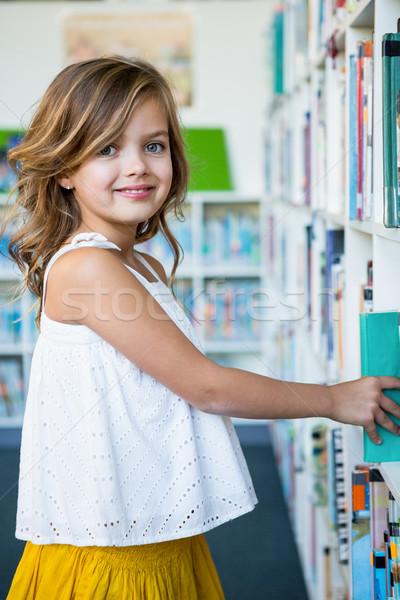 Happy girl searching books in school library Stock photo © wavebreak_media
