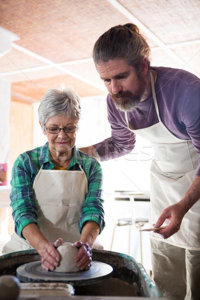 Male potter assisting female potter while making pot Stock photo © wavebreak_media