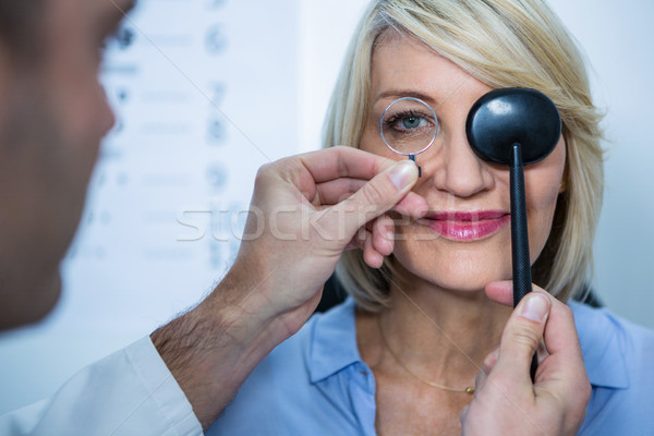 Optometrist examining female patient with medical equipment Stock photo © wavebreak_media
