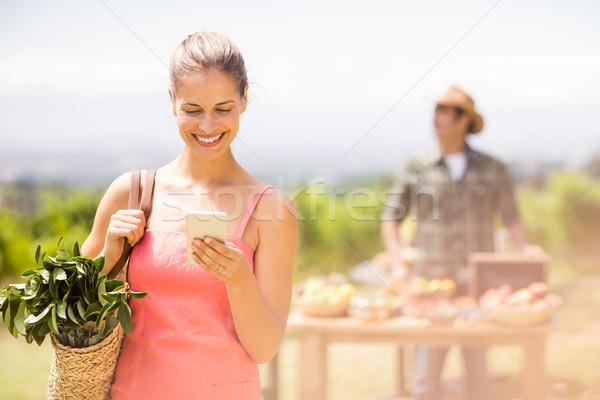 Female customer using mobile phone in front of vegetable stall Stock photo © wavebreak_media