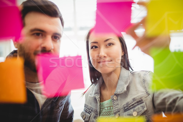 Business people looking at multi colored sticky notes on glass Stock photo © wavebreak_media