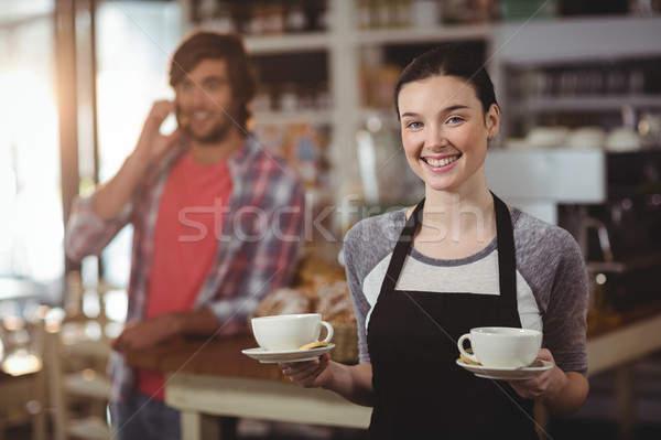 Portrait of waitress holding coffee cups Stock photo © wavebreak_media
