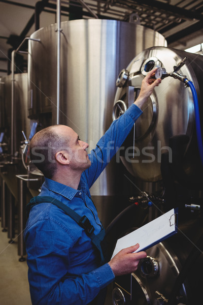 Owner checking meter gauge on machinery Stock photo © wavebreak_media