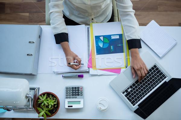Kobieta interesu za pomocą laptopa piśmie notatnika biuro komputera Zdjęcia stock © wavebreak_media