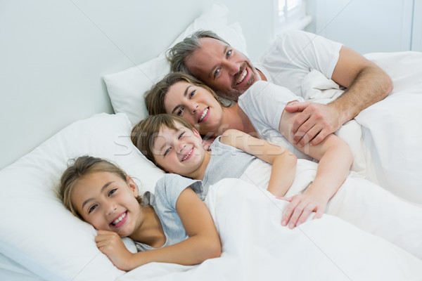 Happy family lying together on bed in bedroom at home Stock photo © wavebreak_media