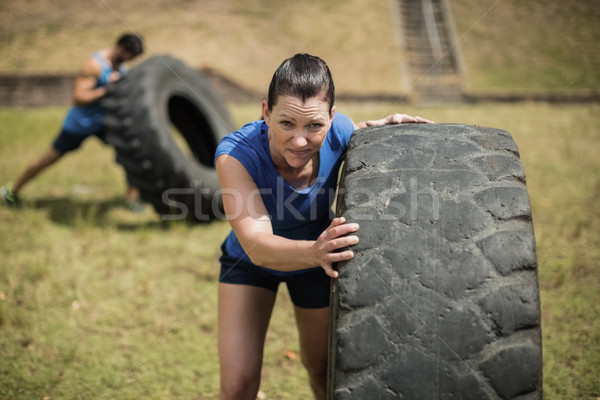 Fit woman flipping a tire during obstacle course Stock photo © wavebreak_media
