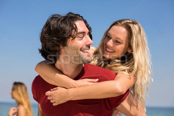 Boyfriend piggybacking girlfriend at beach against sky Stock photo © wavebreak_media