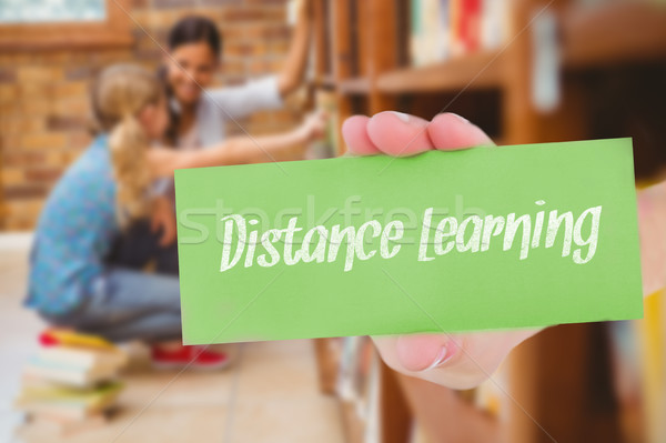 Distance learning against teacher and little girl selecting book Stock photo © wavebreak_media