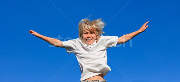 Aranyos gyerek ugrik levegő szabadtér kék ég Stock fotó © wavebreak_media