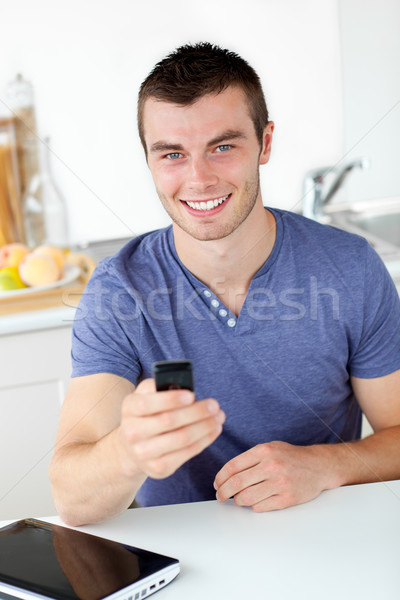 élénk fiatalember küldés szöveg mosolyog kamera Stock fotó © wavebreak_media