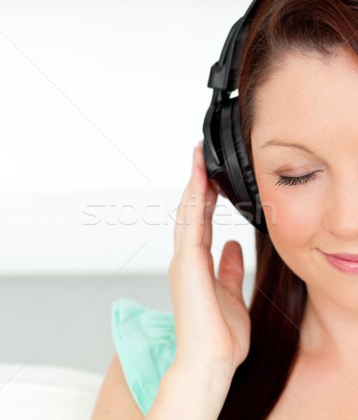 Encantado mulher ouvir música fones de ouvido casa sala de estar Foto stock © wavebreak_media