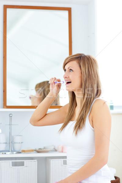 Blond young woman brushing her teeth in the bathroom Stock photo © wavebreak_media