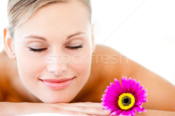 Stock photo: Close-up of a bright woman lying on a massage table with a flower in a health spa